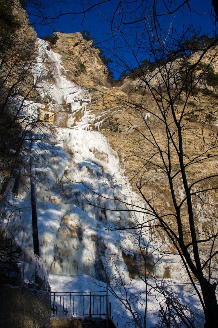 Летом водопад почти полностью пересыхает, а сейчас покрылся ледяной глазурью