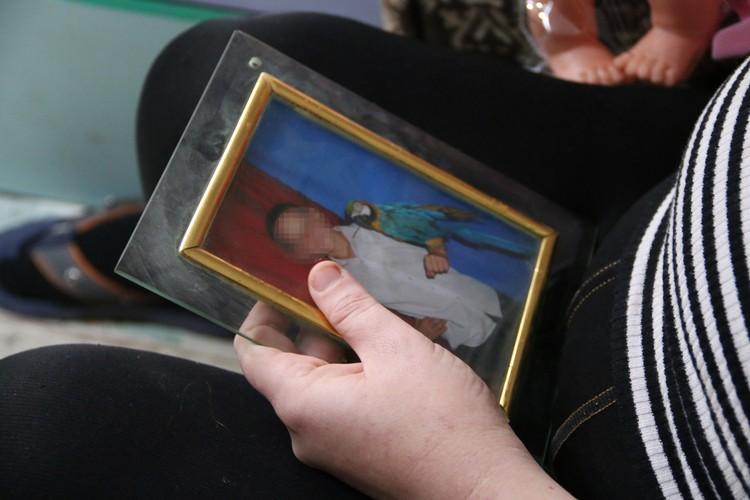 Елена с грустью рассматривает фотографии малышей