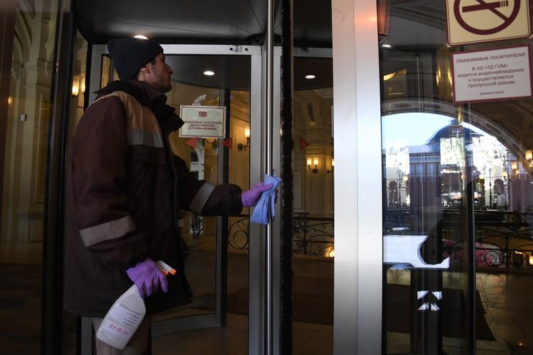 Сотрудник протирает двери ТЦ ГУМ дезинфицирующим раствором