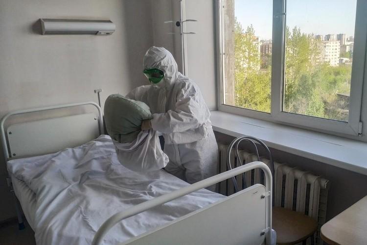 Медсестра в противочумном костюме меняет белье.