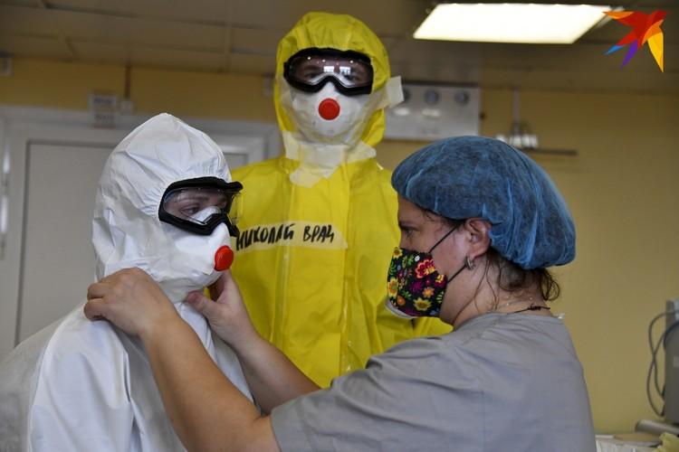 """Перед входом в в """"красную зону"""" медсестра обязательно заклеивает все стыки на одежде специальной липкой лентой."""