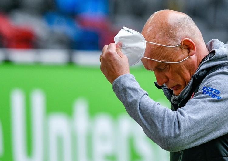 Все тренеры, находящиеся на скамеечке запасных, должны быть в масках. На фото наставник «Фортуны» Уве Реслер снимает защитную маску после ничейной игры с «Падерборном» (1:1). Обе команды находятся в зоне вылета.