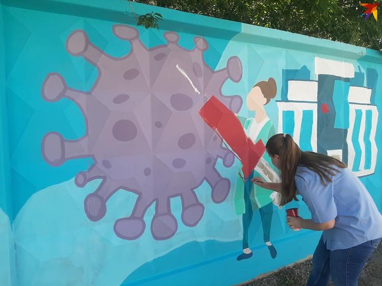 Девушки уже 15 часов рисуют эту десятиметровую картину.