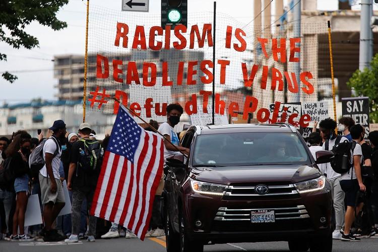 """Участники протестов выходят под лозунгом о том, что """"расизм - самый смертельный вирус"""" и требуют урезать полицейское финансирование."""