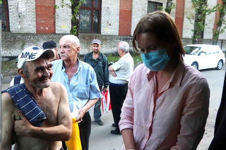 Даша Реут осматривает тех, кто пришел к стоянке автобуса за помощью. Фото: Диана Миндубаева