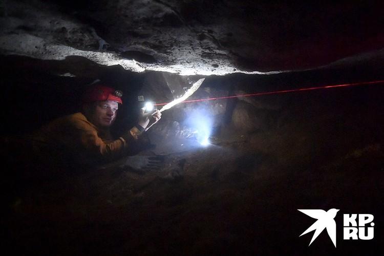 Дмитрий Альбов измеряет лазерной рулеткой новую часть пещеры. Через специальное приложение в смартфоне позже она будет добавлена на карту.