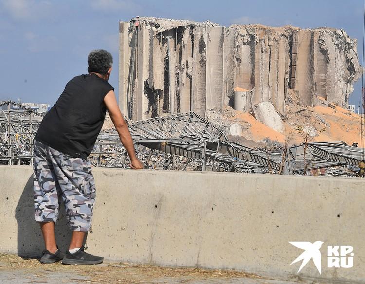 Мужчина рассматривает полуразрушенное бетонное здание элеватора в порту Бейрута.