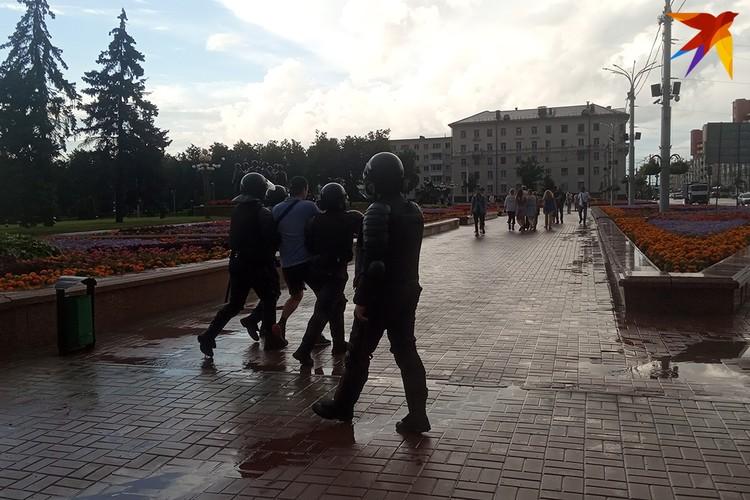 Дождь закончился. В автозак ведут мужчину. Со стороны непонятно, почему именно он привлек внимание сотрудников милиции.