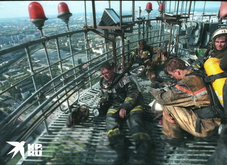 Спасатели отдыхают на техническом балконе башни.