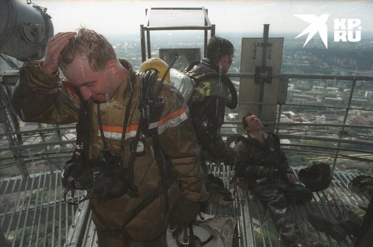Спасатели умываются и поливают себя водой.