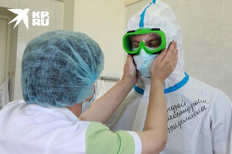 Младший медперсонал иркутской городской клинической больницы No 1 подготавливает к рабочей смене эпидемиолога Андрея Калашникова.