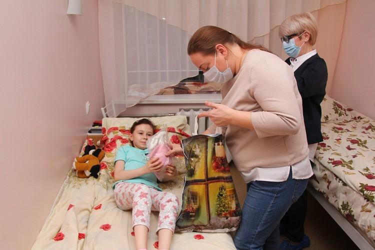 Исполнительный директор организации Ольга Рустамова вручает подарок одной из пациенток