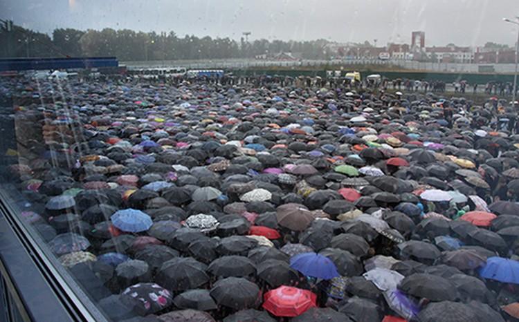 Плотный дождь, кажется, сплотил людей. Тесно, сдвинув зонты, все стоят на тротуарах, проезжей части, на площади.