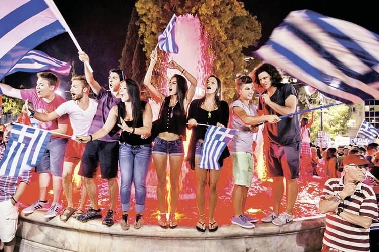 Сторонники отказа платить по кредитам празднуют результаты референдума на улице в центре Афин